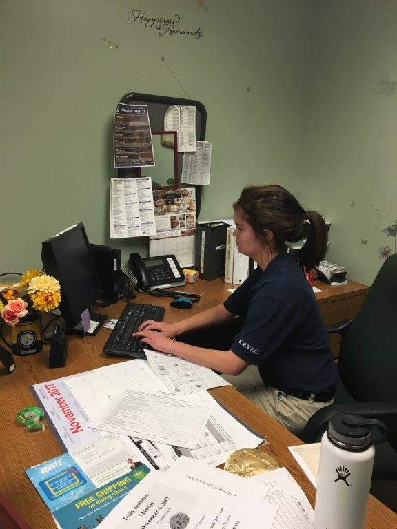 Student working at nursing home desk.